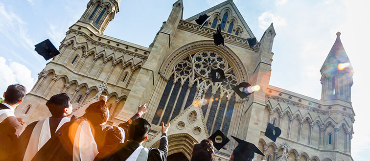 Graduates celebrating their University of Hertfordshire Award by St Albans Cathedral