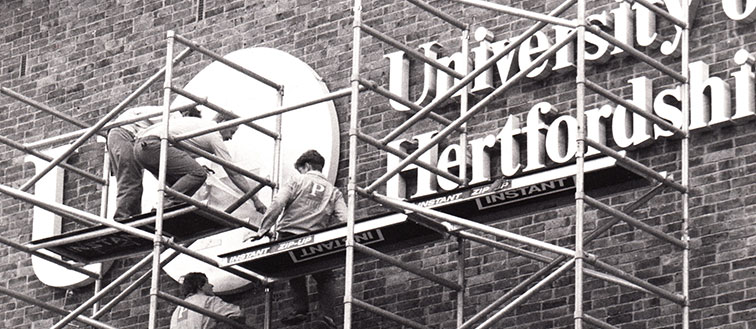 The new University of Hertfordshire sign is put in place.