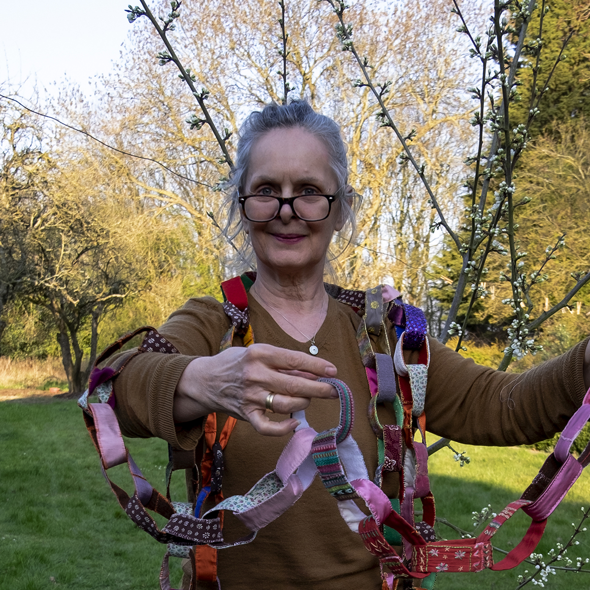a picture of artist Jane Glynn wrapped around colourful paper chains