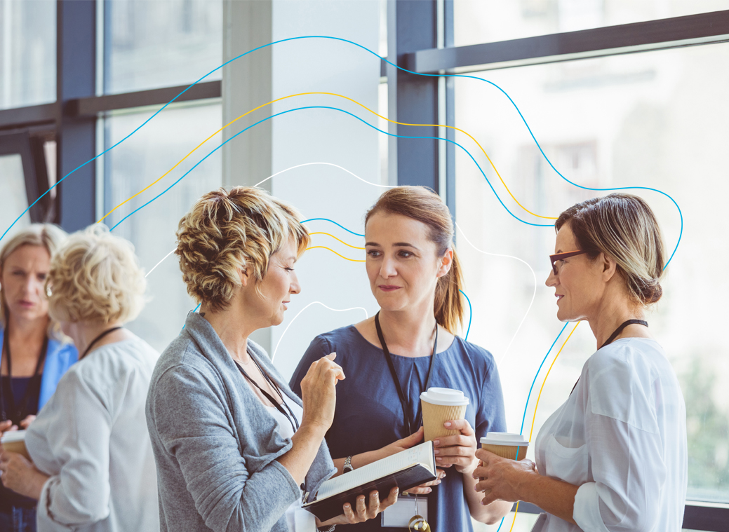 Female colleagues standing and talking with cups of coffee