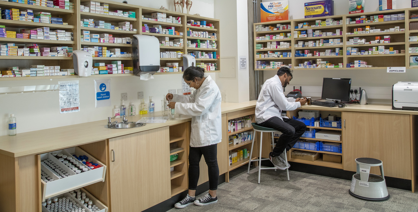 Students in pharmacy lab looking at medicines