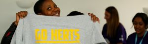 A student holding up a Go Herts hoodie