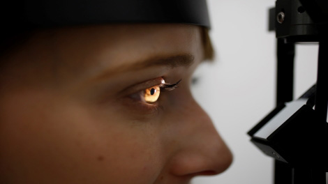 a close up of a student's eye. a light is shining into it for the eye exam