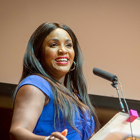 a woman smiles as she talks at a podium