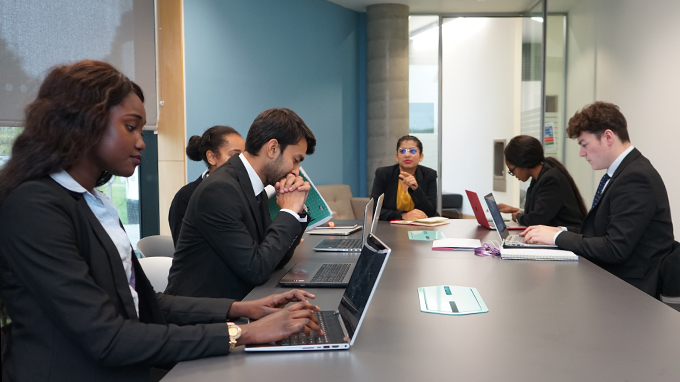 students sit around a table. They are smartly dressed and some work on their laptops