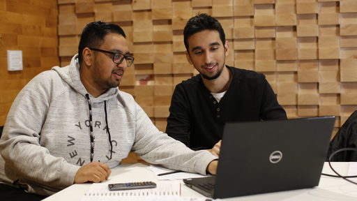 Two male students using laptop