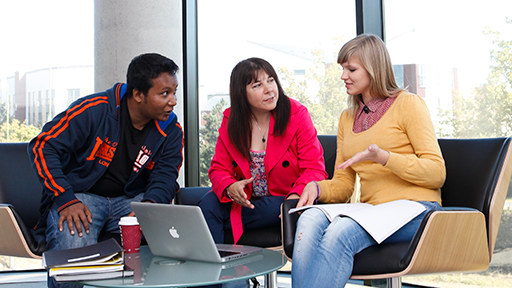 Three people sit around a table with laptops and papers having a discussion
