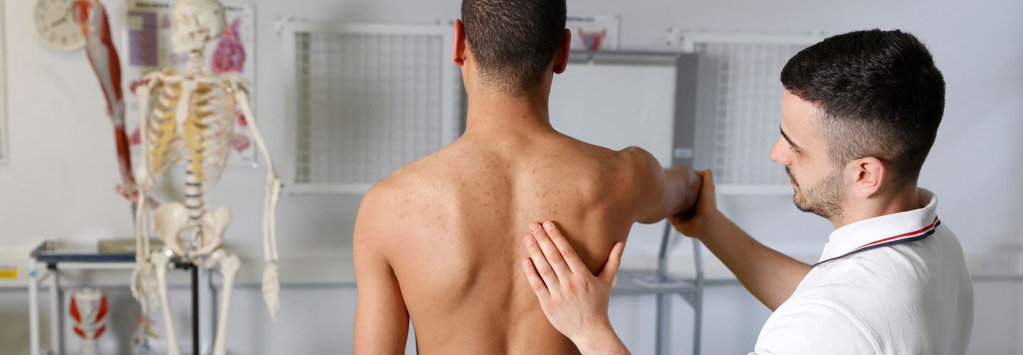 Physiotherapy student manipulating a patients shoulder