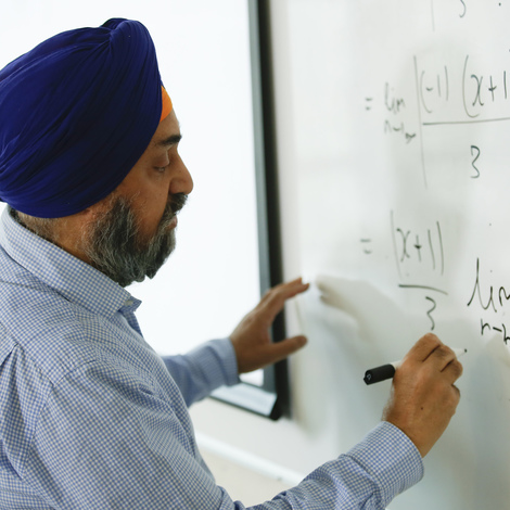 Researcher writing equations on board