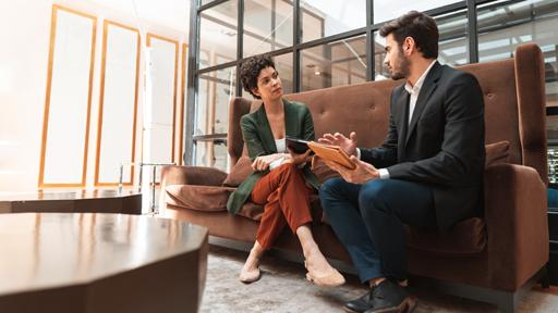 Man and woman talking on sofa