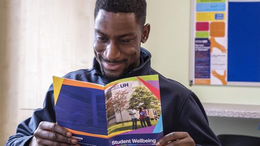 Black male student reading leaflet