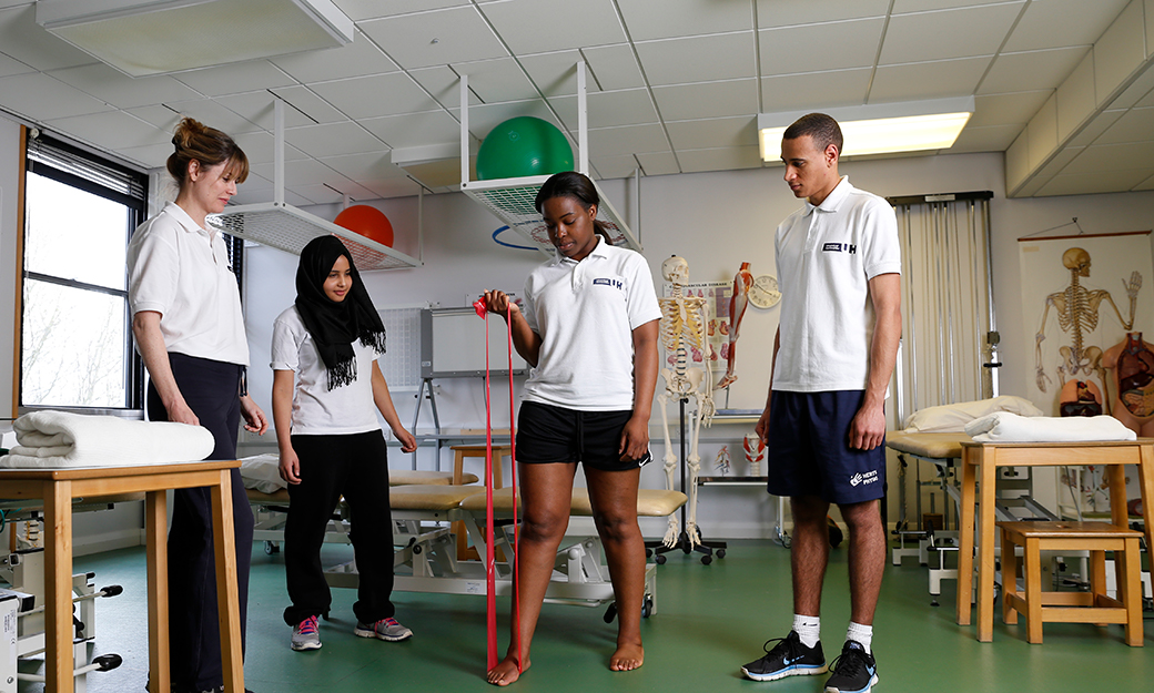 A student stands with a band under her foot to test muscle strength