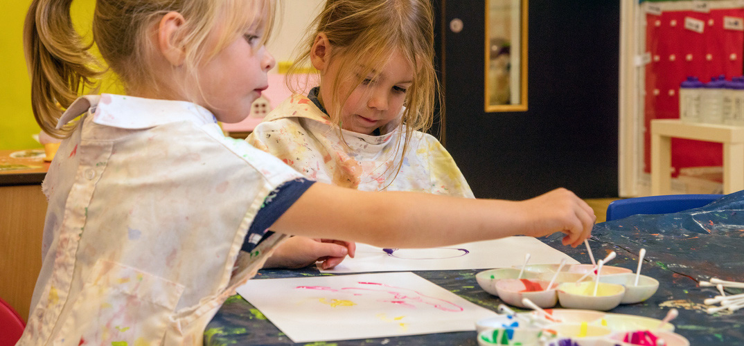 Two nursery children painting