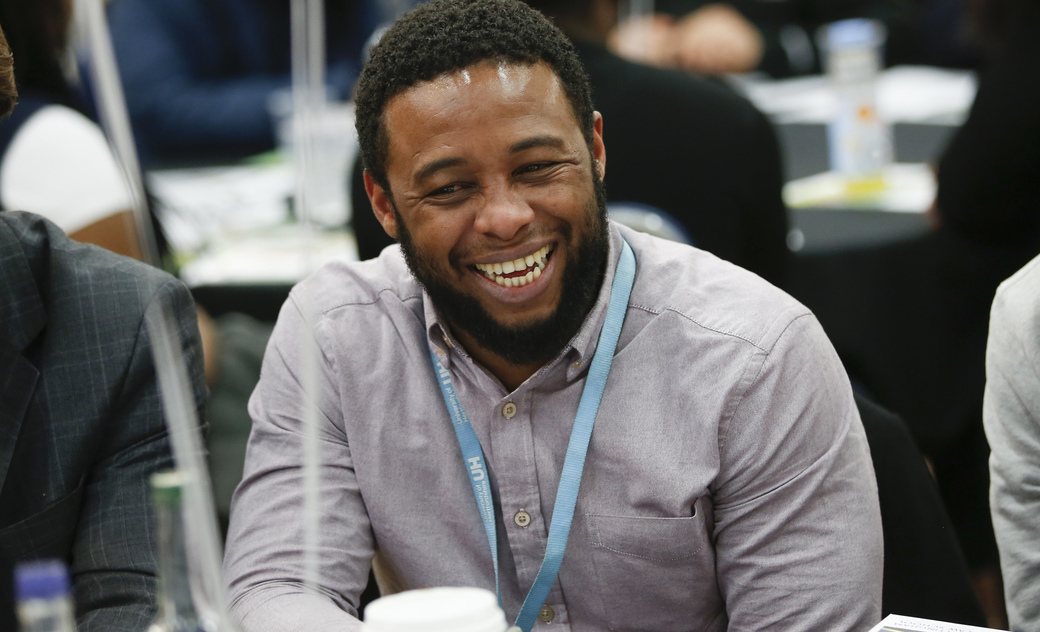male student at a conference smiling