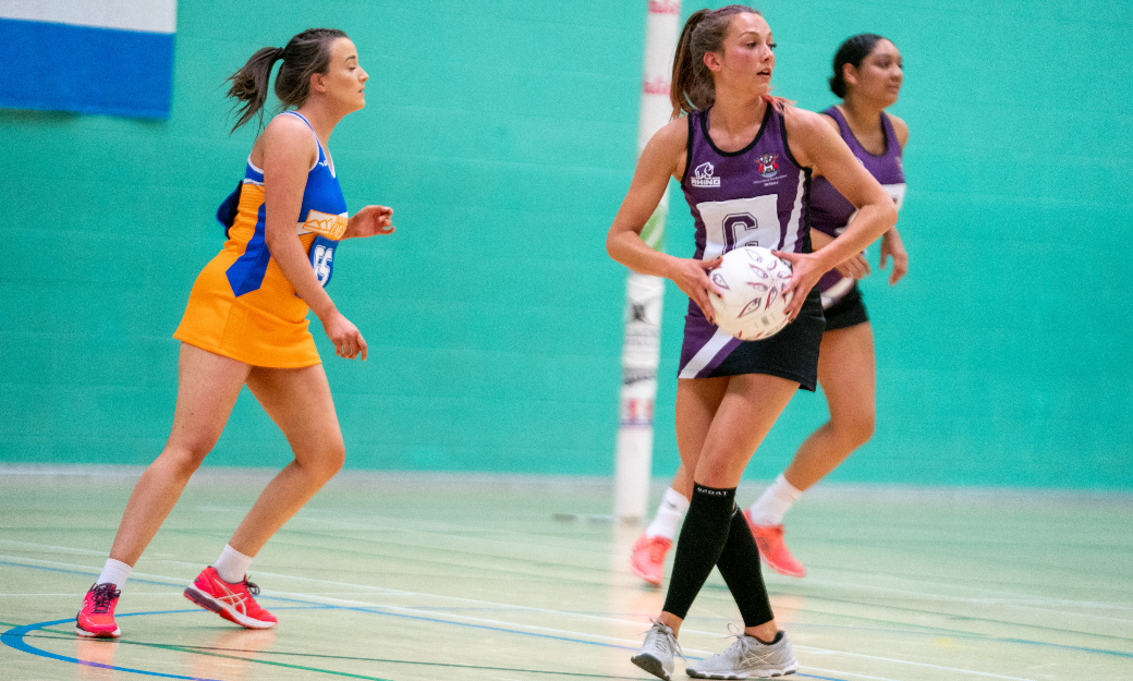 Female netballers playing game in sports hall