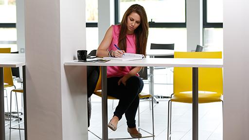 a woman sits on a bar stool writing