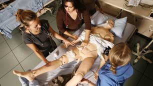 Medical students tending  a patient mannequin