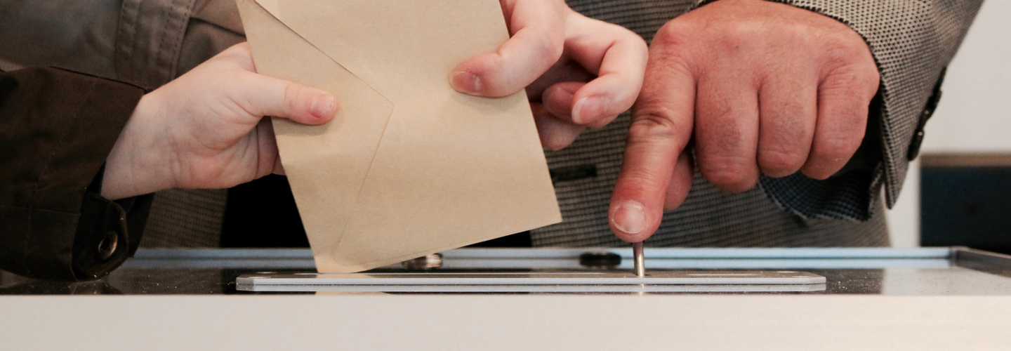 Submitting a vote. Hands holding envelope.