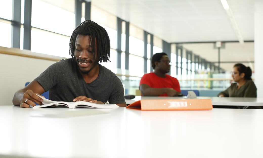 Male student studying with friends in background