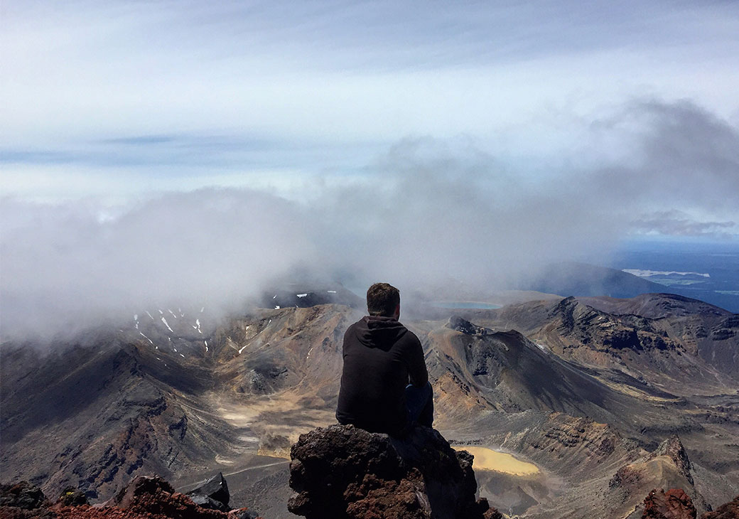 Male student sitting on top of mountain