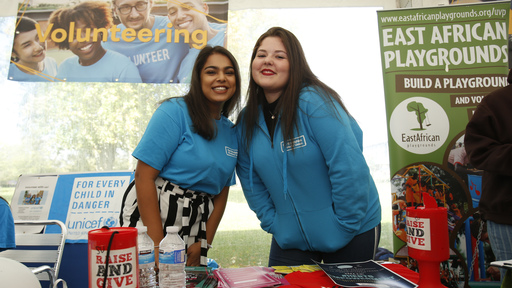 Two female students smiling on fair stand
