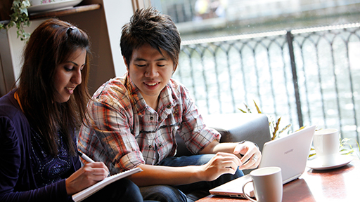 A woman and a man sit in a cafe making notes from their laptop