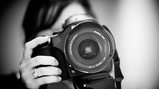 a black and white photograph of female hands holding a camera