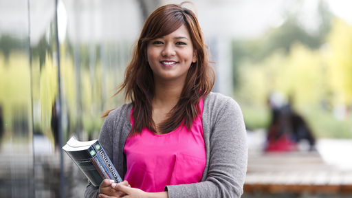 Woman in pink top and grey cardigan holding books