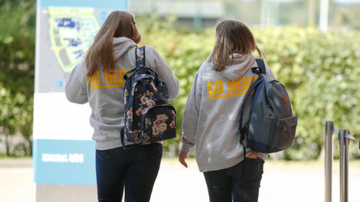 Two students in Go Herts hoodies walk on campus