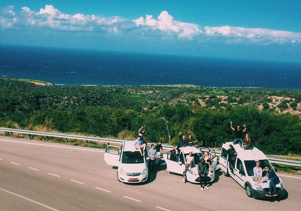 Three vans on road by sea