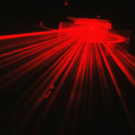 Red laser flare in dark room