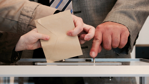 Person putting ballot in ballot box