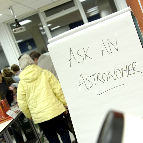 A person walks past a sign which reads 'ask an astronomer'