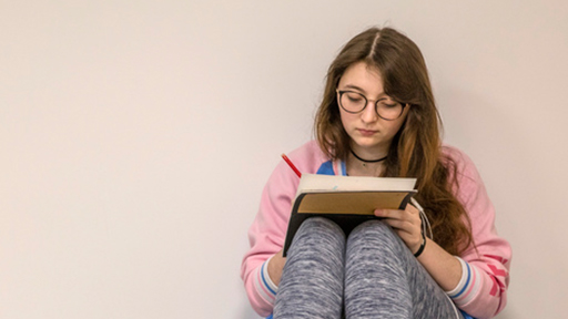 a writes on a notepad which rests on her knees