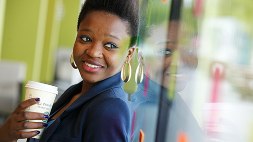 A female students smiles as she looks out of a window