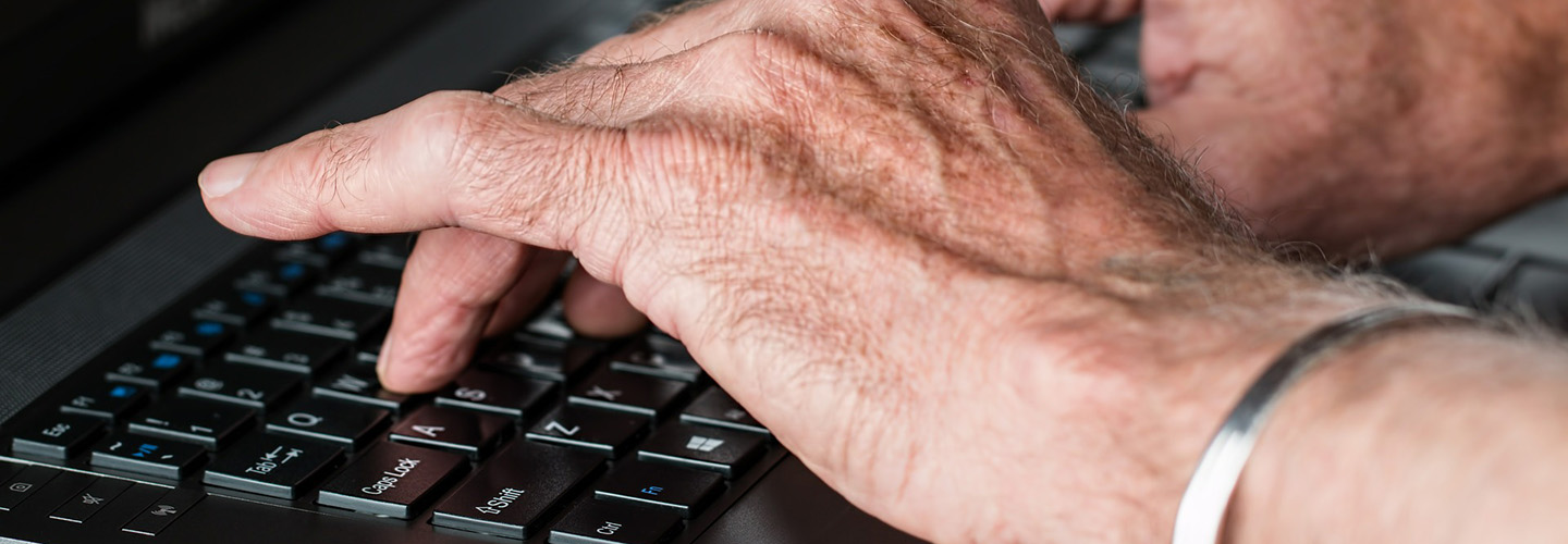 Hands of elderly computer user