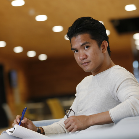 Student with notebook looking at camera