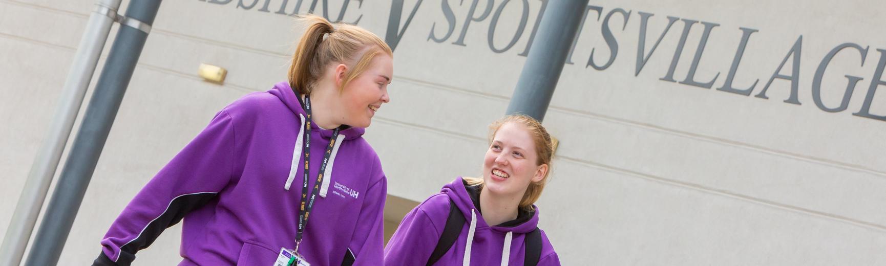 two female sport studies students walking outside the Hertfordshire Sport Village