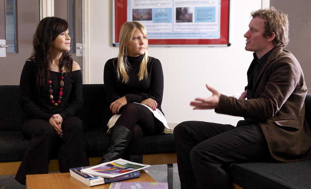 two students in conversation with a lecturer