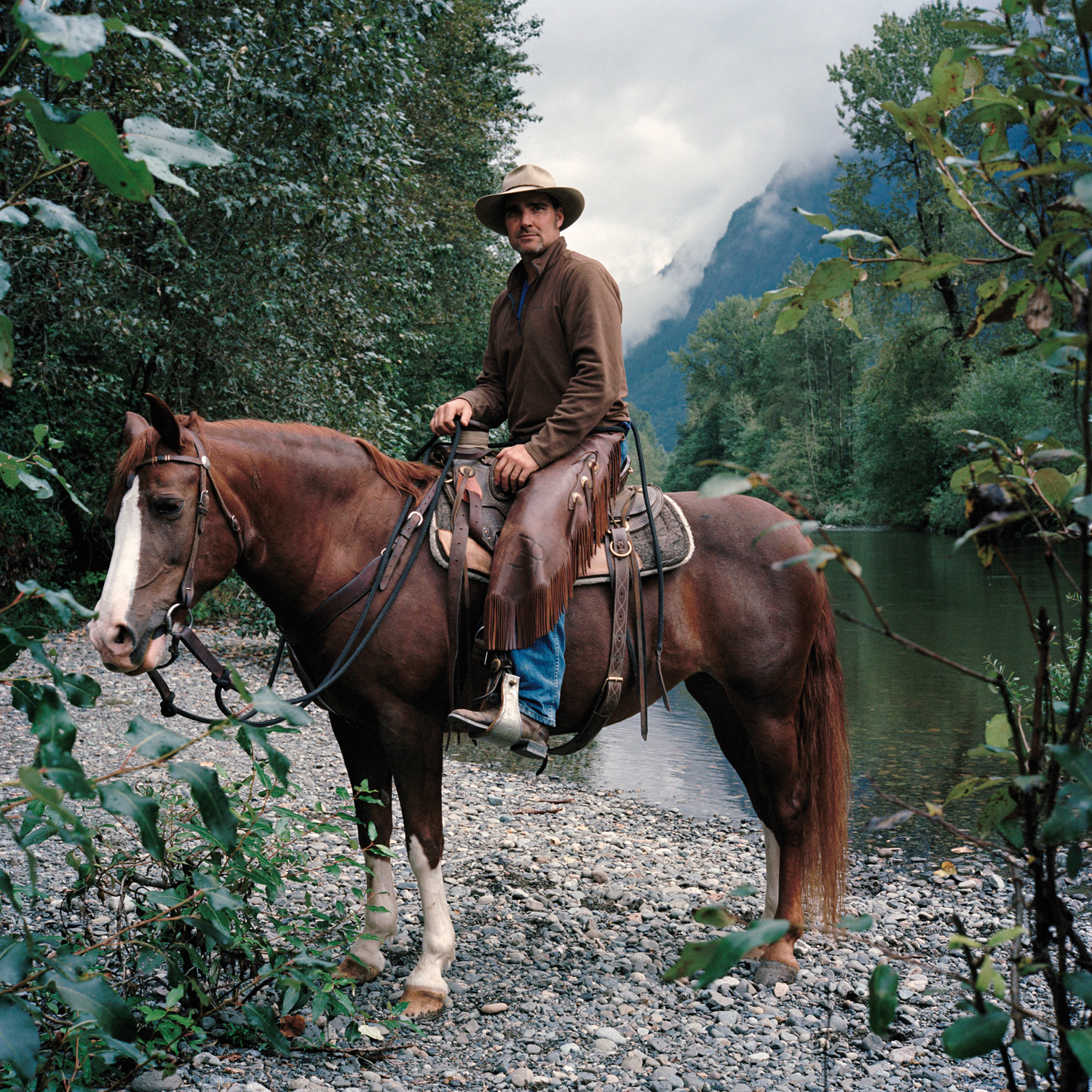 Man sitting on brown horse in brown cowboy outfit, behind him a lake and green trees and mountain