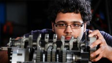 An engineering student working with a mechanical device.