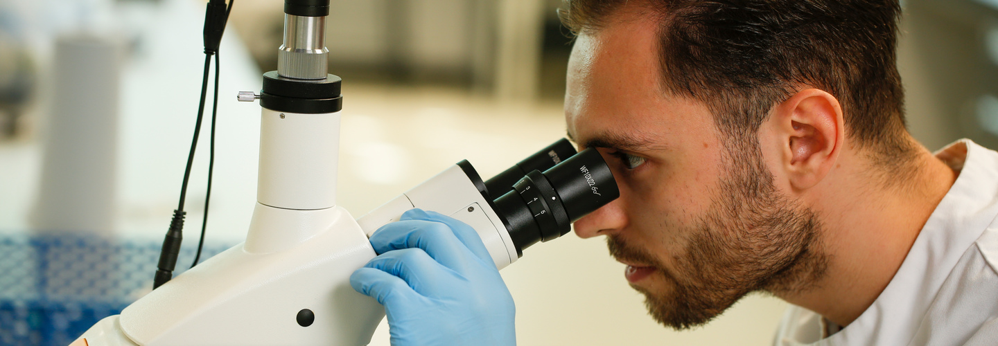A student looking through a microscope