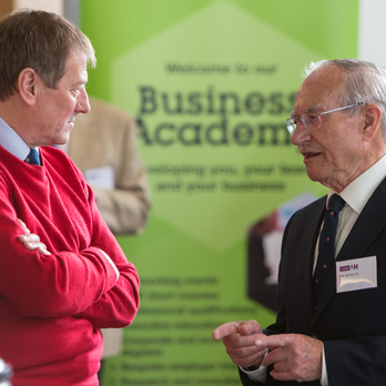 Two men talking at the Business Academy