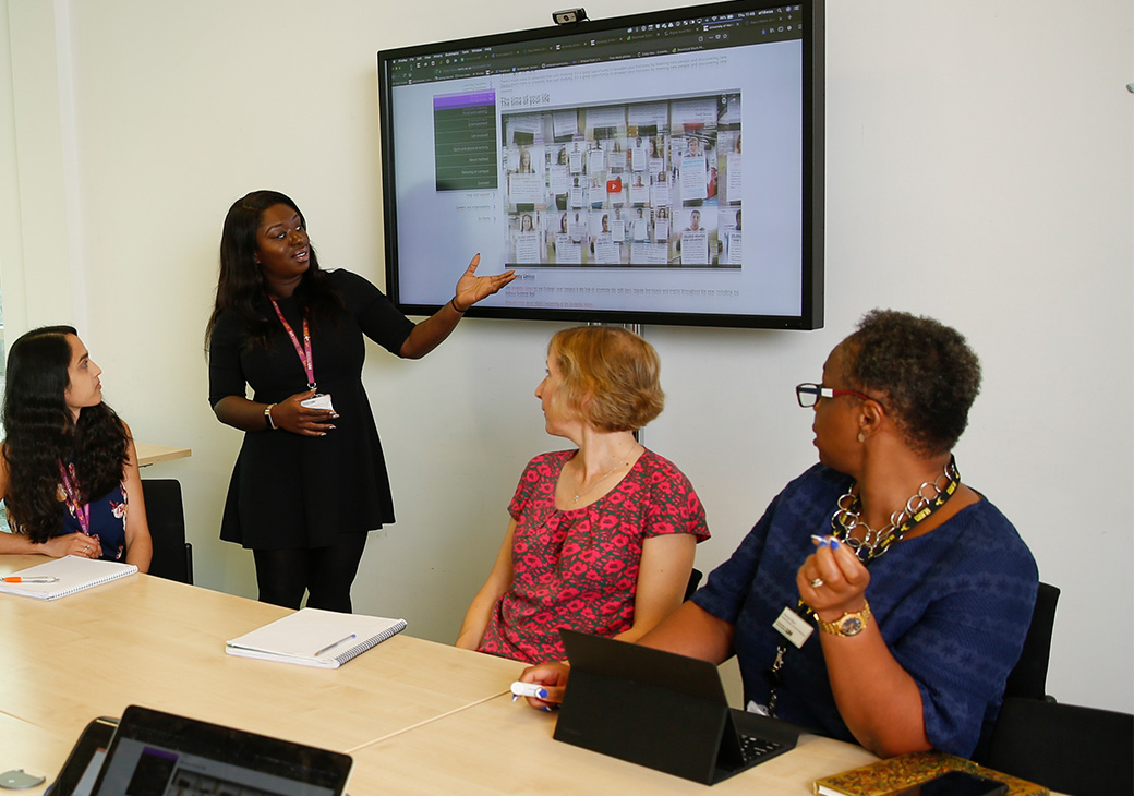 Lady presenting to colleagues on screen
