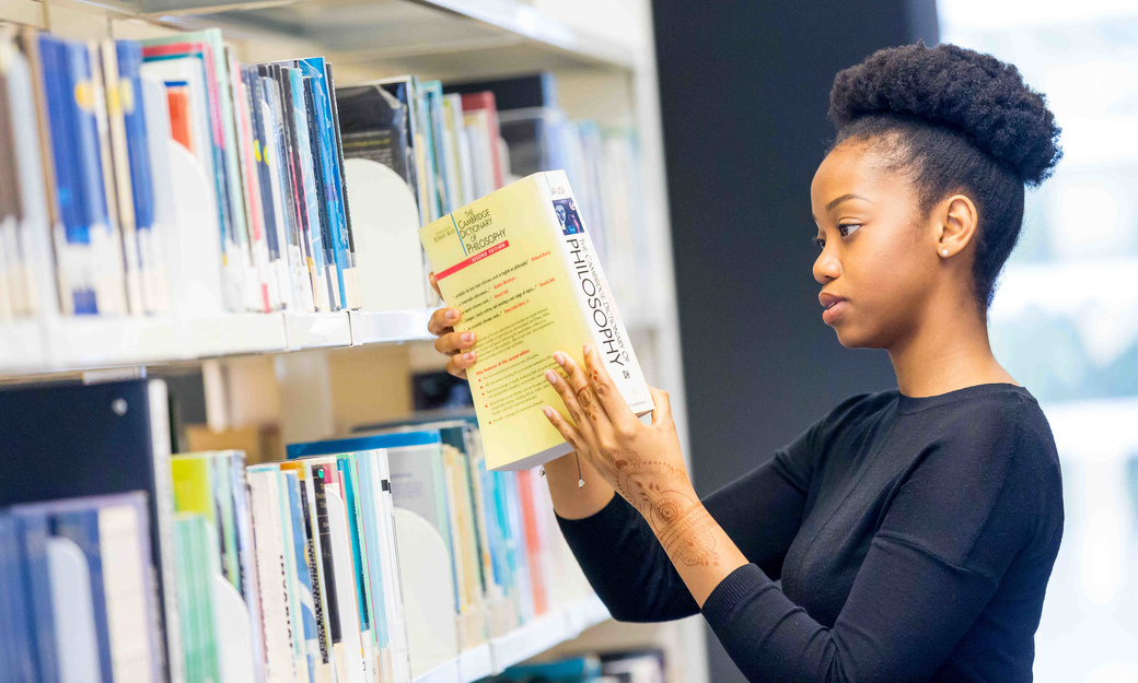 Girl in library with Philosophy book