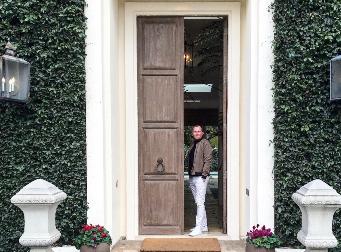 Charlie Edgar standing in door of mansion