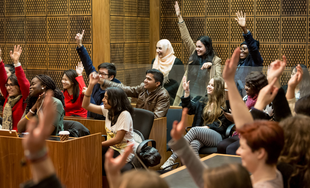 students raise their hand in mock court room