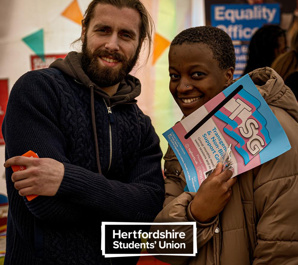 Female and male student holding leaflets on transgender