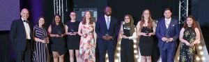 A group of people hold their awards and smile