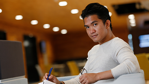 a student sits with a notepad and pen on his lap